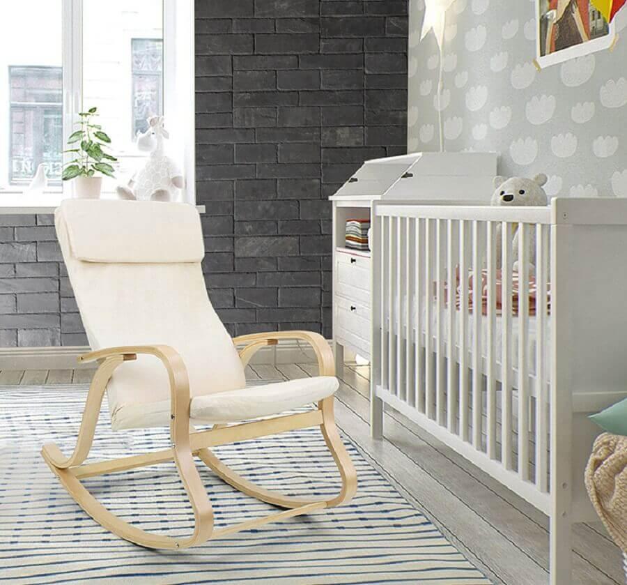 quarto de bebê decorado com tapete listrado e cadeira de balanço de madeira Foto Stonetack