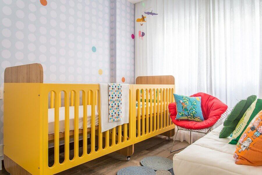 quarto de bebê gêmeos planejado decorado com berço amarelo e papel de parede neutro Foto Natoca Design