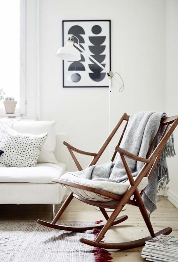 sala decorada com cadeira de balanço de madeira e sofá branco Foto Doc Hendley