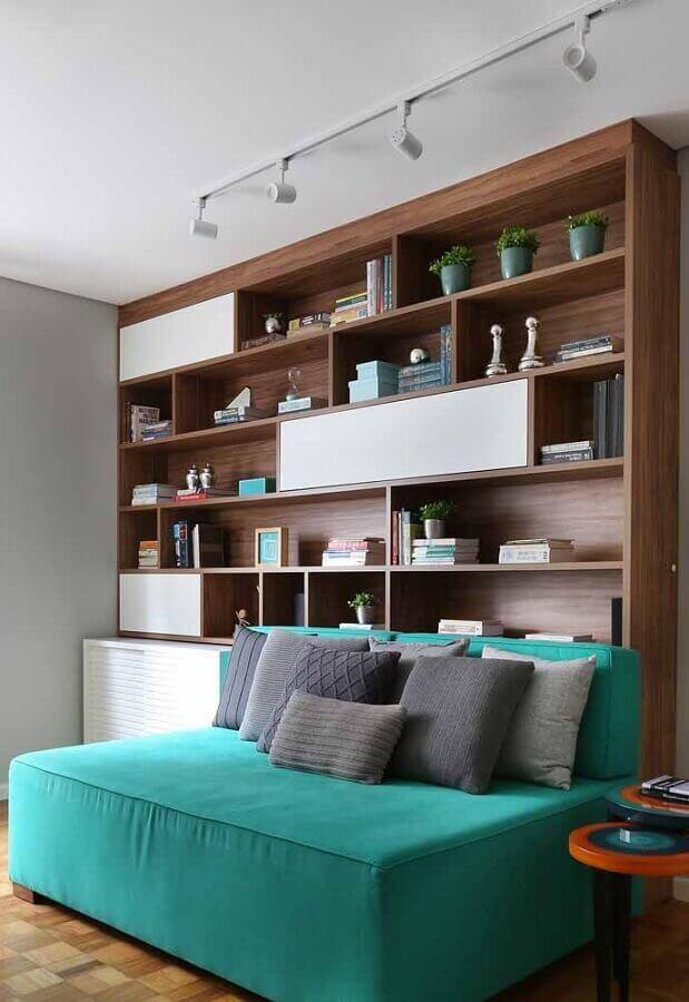 sala decorada com estante planejada de madeira e sofá verde água Foto Pinosy