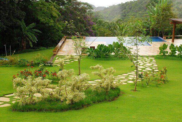 Área externa da casa de chácara com jardim e piscina