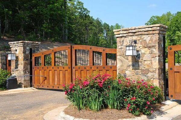 Entrada de chácara composta por um portão de madeira e canteiro de flores