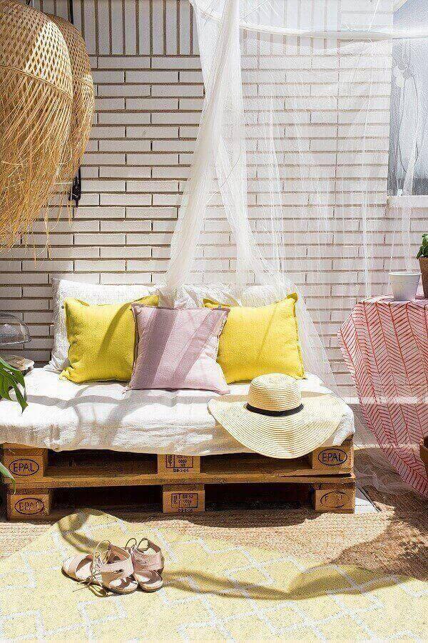 A leveza do branco se harmoniza com as almofadas coloridas da varanda boho