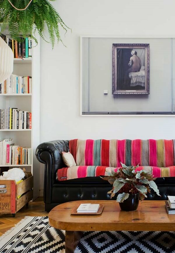 A manta listrada colorida sob o sofá preto trouxe alegria para o ambiente