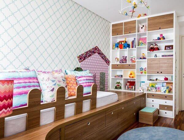 Almofadas coloridas e estante para quarto infantil com nichos