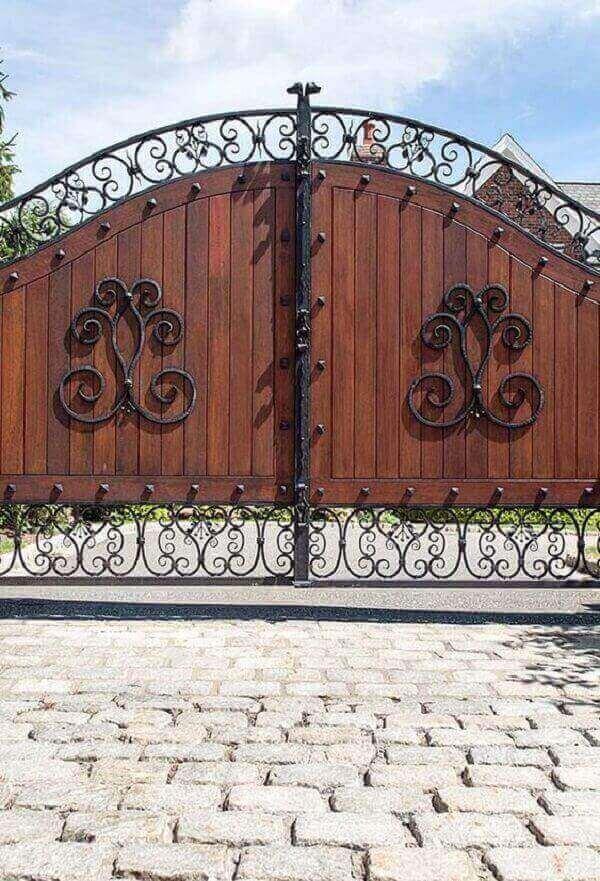Arabescos em ferro compõem a estrutura do portão de entrada de chácara