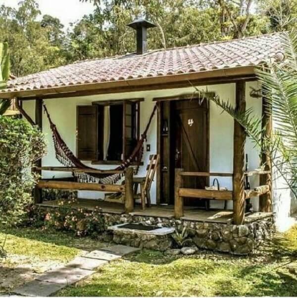 Casa de campo rústica decorada com rede na varanda