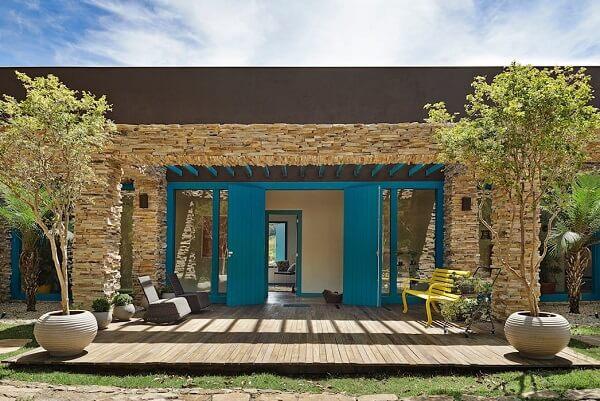 Casa de chácara com fachada de pedras e porta azul