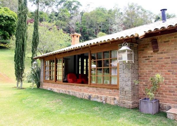 Casa rústica com acabamento externo de pedras e tijolo aparente