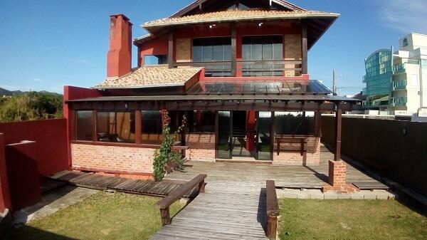 Casa rústica com varanda de piso de madeira