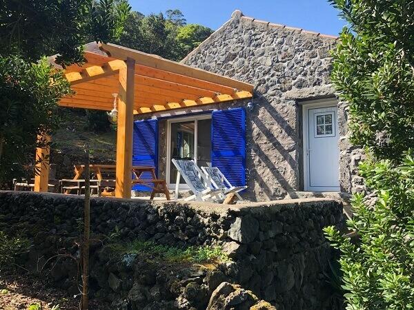 Casa rústica de pedras e pergolado de madeira natural