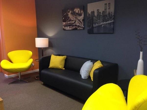 Complemente a decoração do escritório com sofá preto e almofada amarela