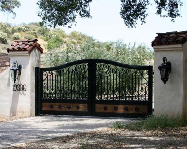 Design de ferro e madeira compõem o portão para entrada de chácara