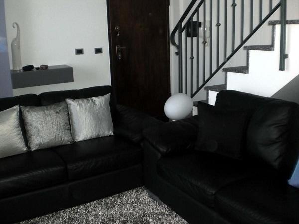 Dois conjuntos de sofá preto de 2 lugares complementam a decoração da sala