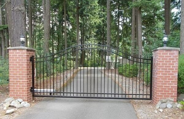 Entrada de chácara com parede de tijolinho aparente e portão de ferro