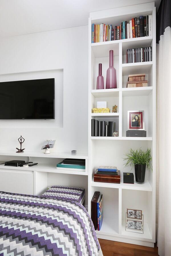Estante branca com nichos se harmoniza com o espaço para televisão