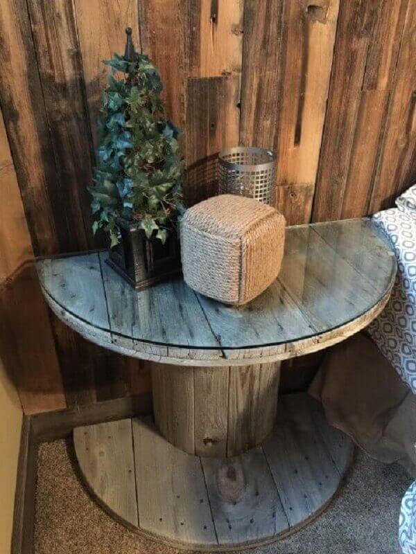 Mesa de carretel de madeira com vidro como criado-mudo ao lado da cama