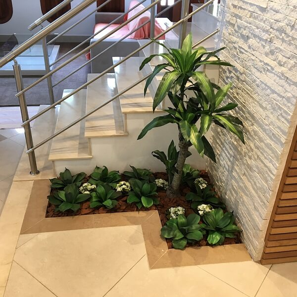 Mini jardim ao pé da escada feito com plantas artificiais