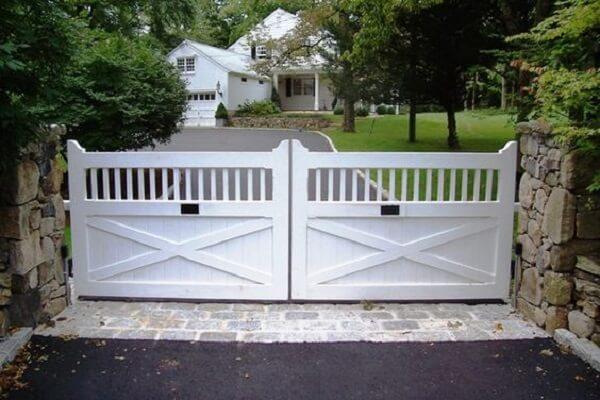 Muro feito de pedras e portão em madeira branca compõe a entrada de chácara
