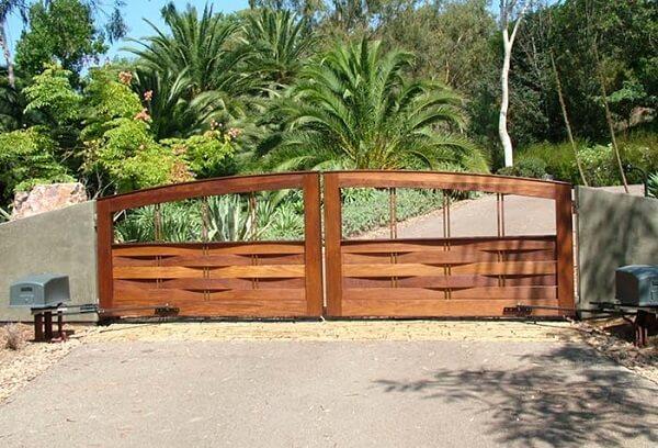 O portão de madeira fixado no muro de concreto dá acesso a entrada de chácara