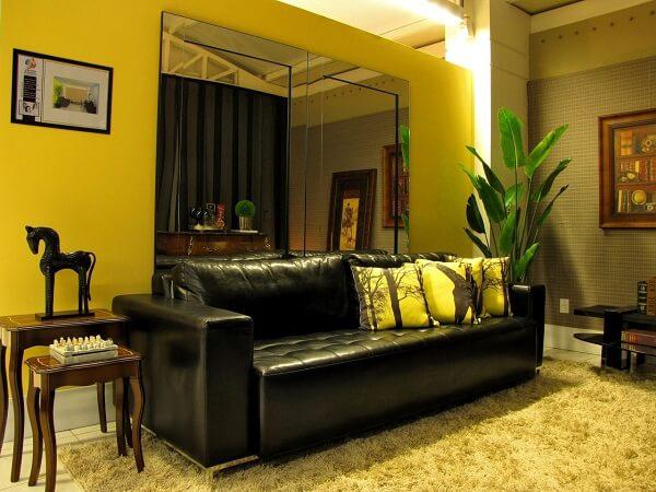 O sofá de couro preto equilibra o ambiente da sala com parede na cor amarela