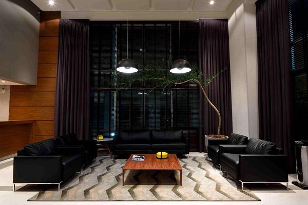 O sofá preto de couro se harmoniza com a tonalidade das cortinas