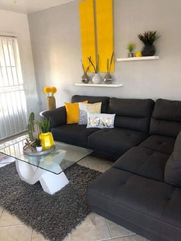 O sofá preto utilizado nesta sala neutraliza acessórios em tom amarelo
