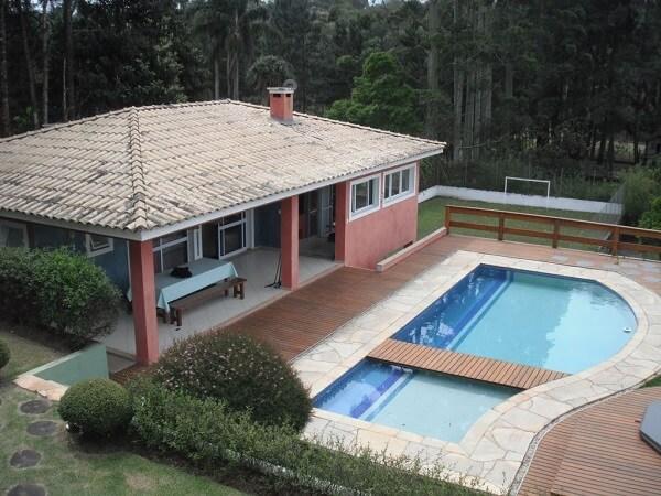 Parede com pintura vermelha e piscina com deck compõem a casa de chácara