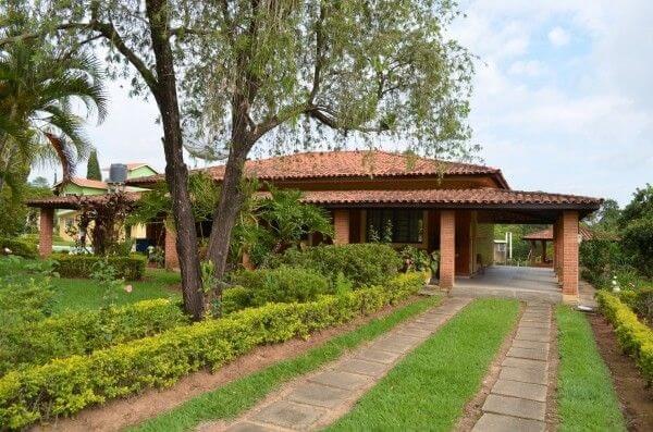 Paredes de tijolinho comum e canteiro com arbustos fazem parte da casa de chácara