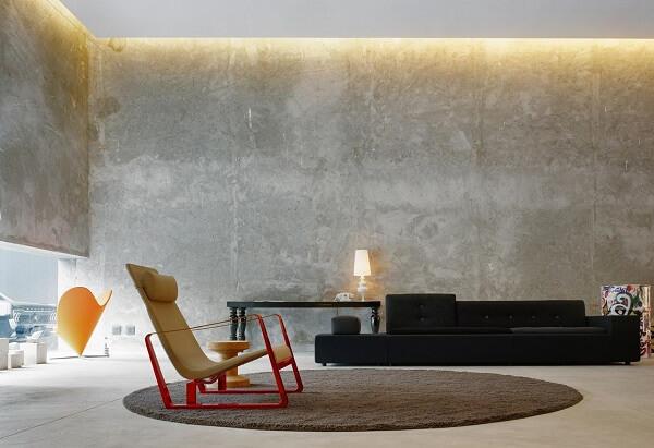 Paredes na cor concreto, sofá preto e tapete marrom complementam a decoração