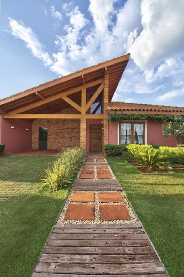 Piso com tacos de madeira e parede de tijolinho complementam a decoração da casa da chácara