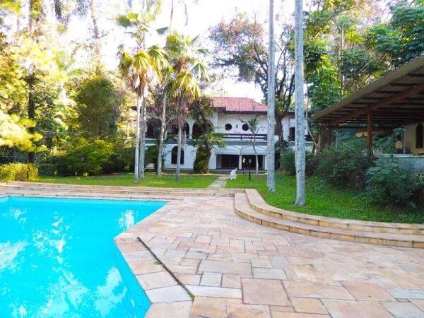 Piso de pedra natural e arbustos naturais verdes complementa a decoração da casa de chácara