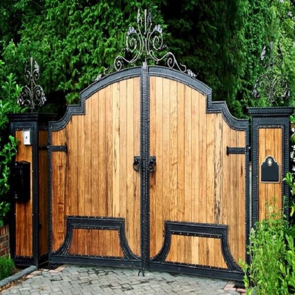 Portão alto em madeira e ferro compõe a entrada de chácara