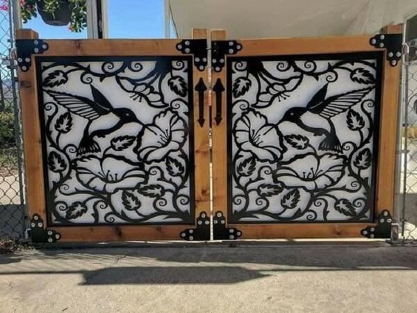 Portão com design de beija flor compõem a entrada de chácara