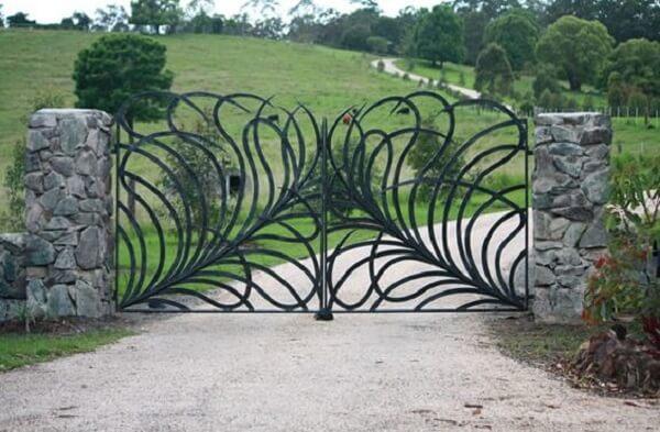 Portão com formas orgânicas compõem a entrada de chácara