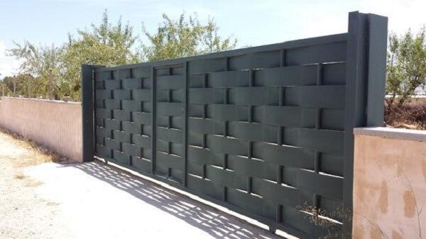 Portão de alumínio trançado na cor preta compõe a entrada de chácara