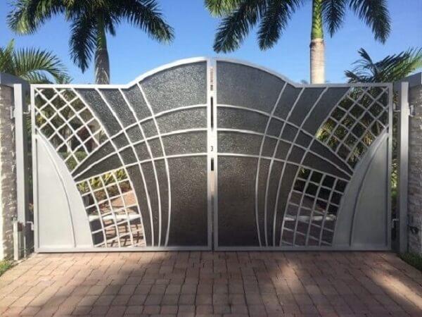 Portão de ferro mesclando as cores preto e cinza compõem a entrada de chácara