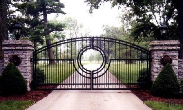 Portão de ferro vazado ao centro compõem a entrada de chácara