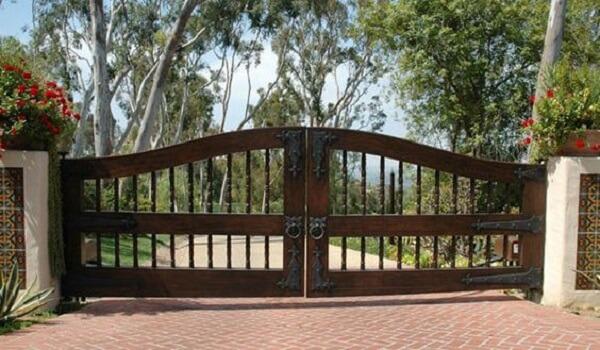 Portão de madeira com alças de ferro utilizados na entrada de chácara