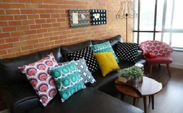 Que tal, sofá preto, almofadas coloridas e parede de tijolinhos?