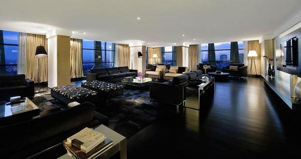 Sala ampla decorada com sofá preto de 3 lugares