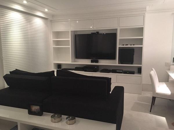 Sala de estar com móveis na cor branco e sofá preto de 2 lugares