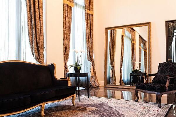 Decoração clássica com sofá preto e espelho