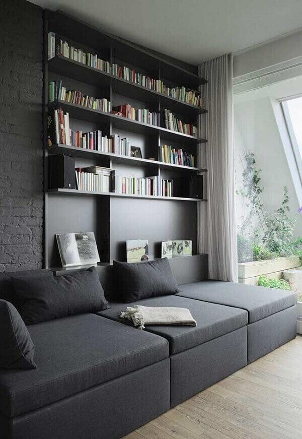 Sofá de canto preto conectado a prateleira de livros