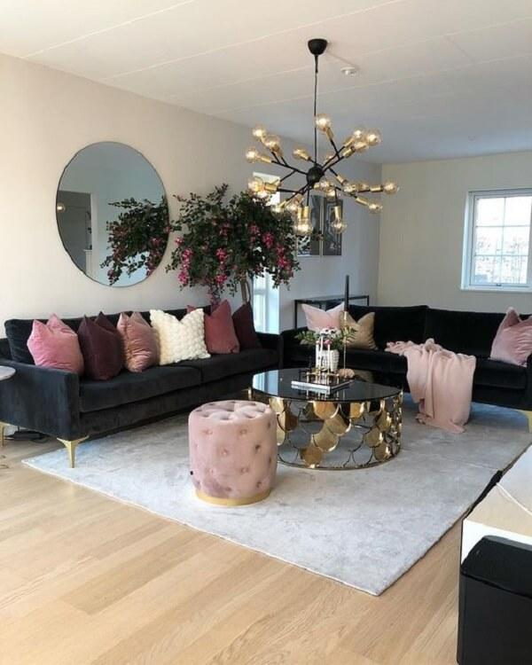Sofá preto com pés dourados decorando a sala de estar