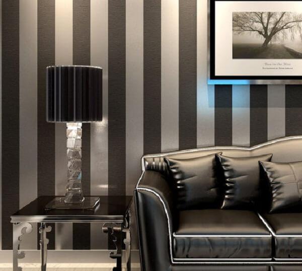 Sofá preto com papel de parede listrado transmite elegância