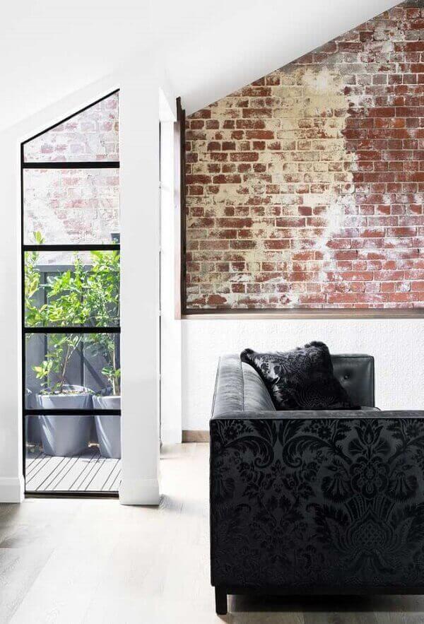 Sofá preto com tecido em textura complementa a decoração do ambiente