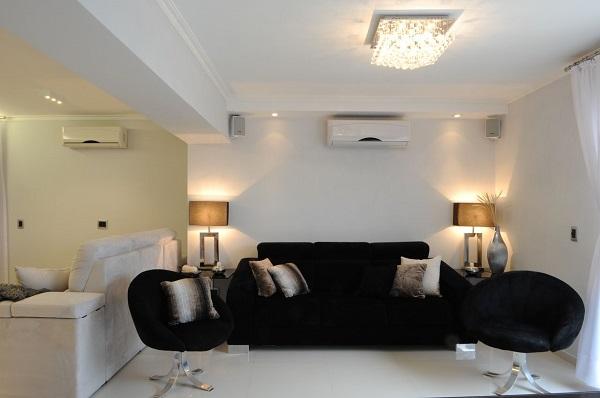 Sofá preto e lustre com cristais complementam a decoração da sala