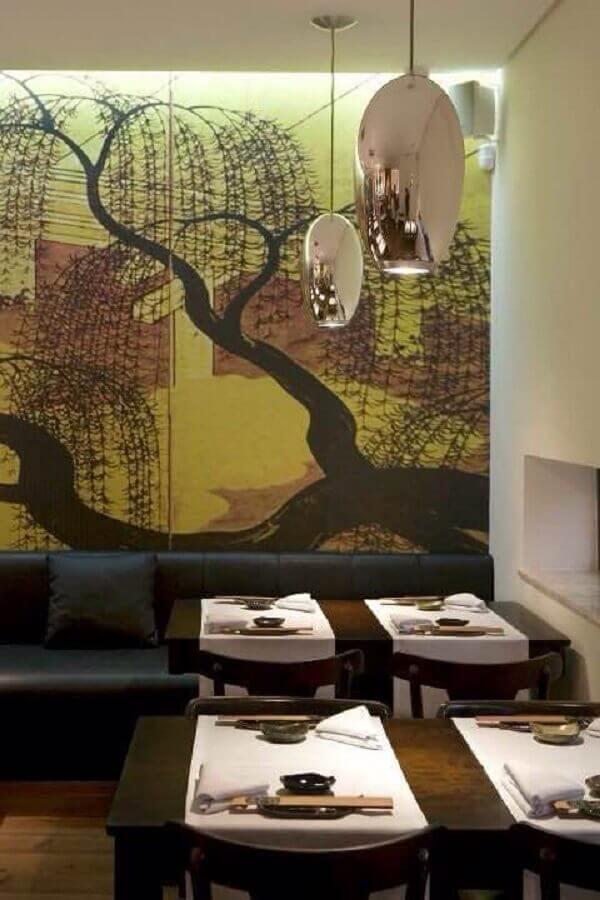 Sofá preto e parede adesivada complementa a decoração do restaurante