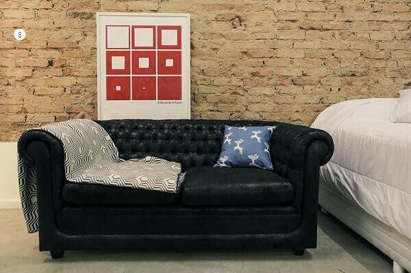 Sofá preto e parede de tijolinhos da sala de estar